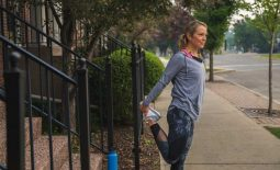 Female runner stretching legs on sidewalk