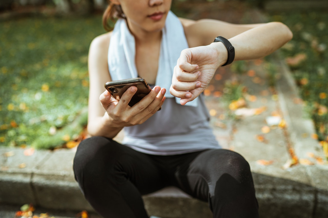 woman looking at stats on fitness watch after workout